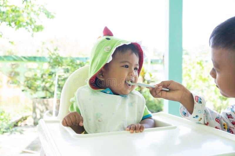 Broer het voeden voedsel aan babyjongen royalty-vrije stock foto's