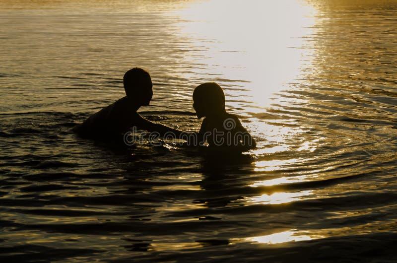 Broers die in het water van een meer bij zonsondergang spelen royalty-vrije stock afbeelding