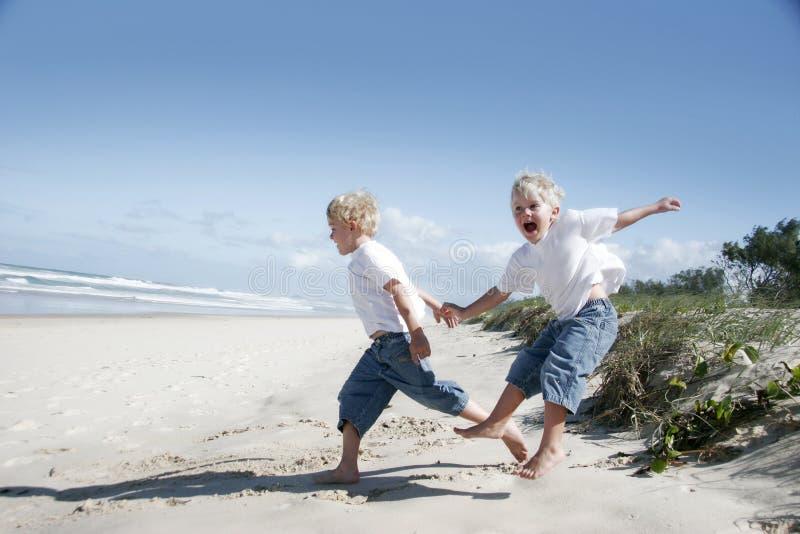 Broers die op het strand spelen royalty-vrije stock afbeeldingen