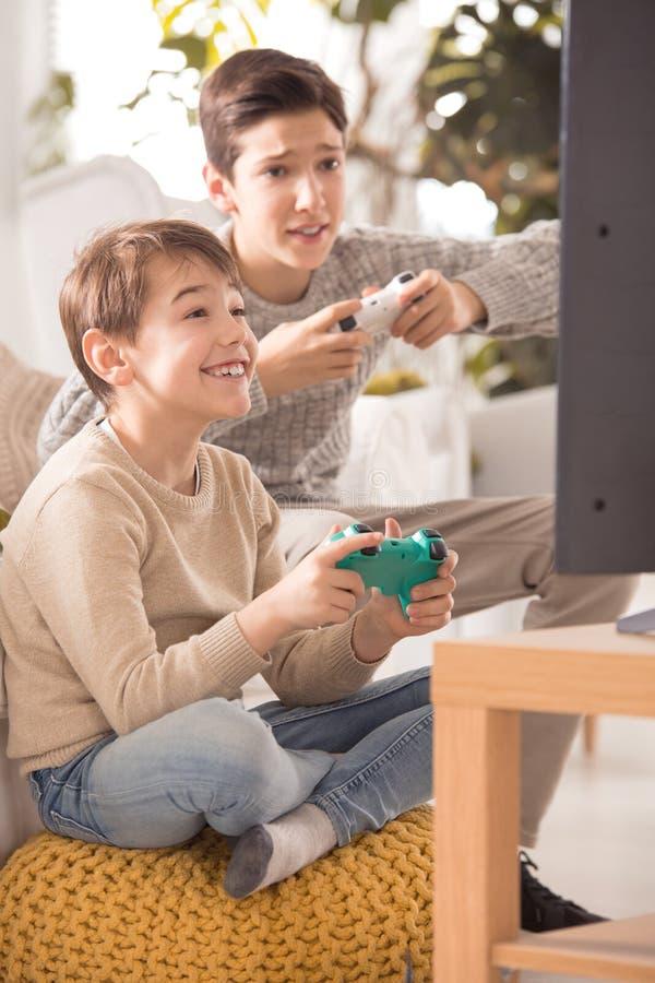 Broers die op playstation spelen stock afbeeldingen