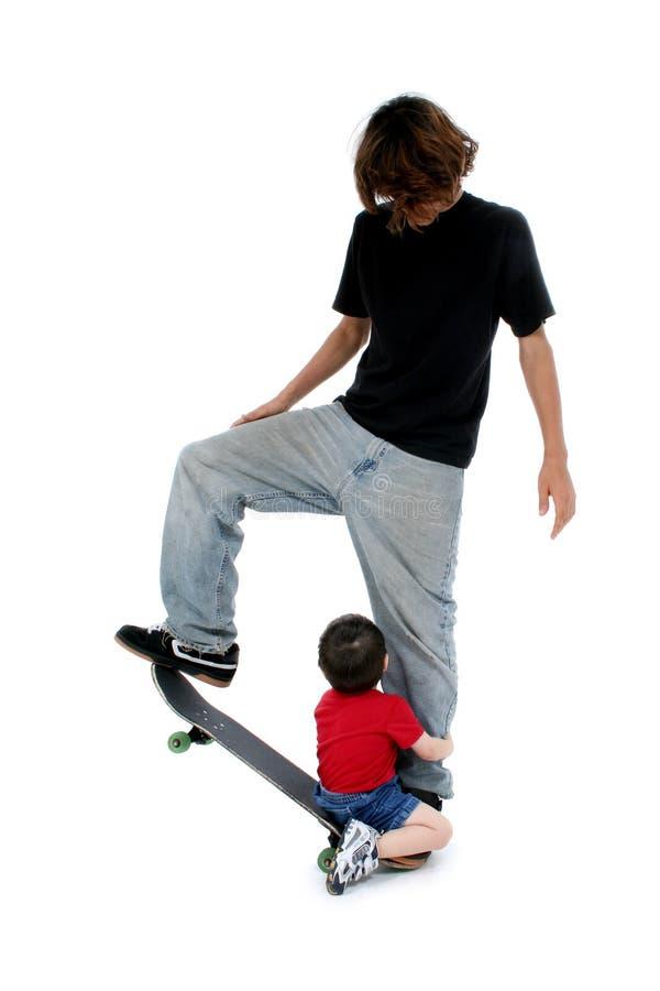 Broers die op Skateboard spelen stock afbeeldingen