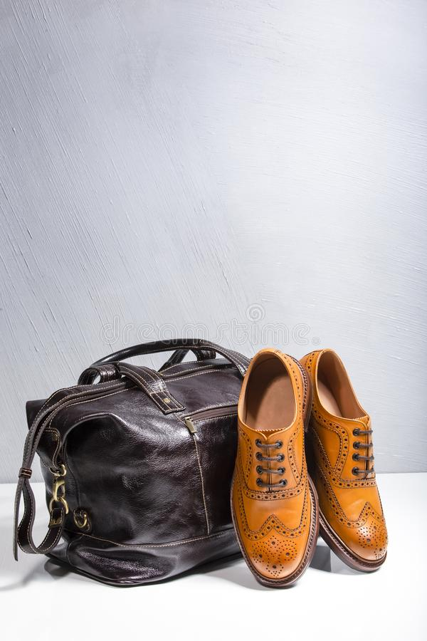 Broggued Oxford Calf Leather Shoes Along With Dark Brown Leather Travel Bag. Footwear and Accessories Concepts. Male Tanned Full Broggued Oxford Calf Leather royalty free stock photos