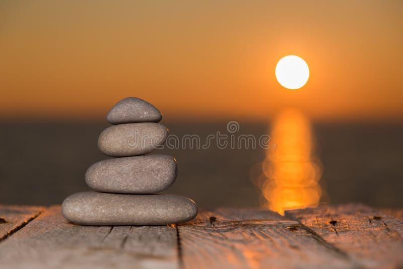 Brogujący otoczaki na drewnianym położenia słońcu i powierzchni zdjęcie royalty free