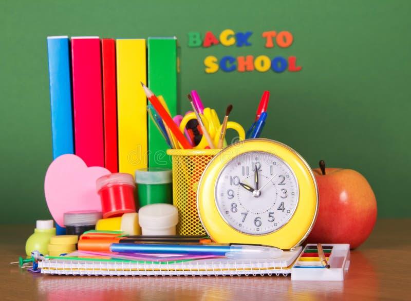 Broguje podręczniki, materiały ustalonego budzika i jabłka na zieleni, zdjęcia stock