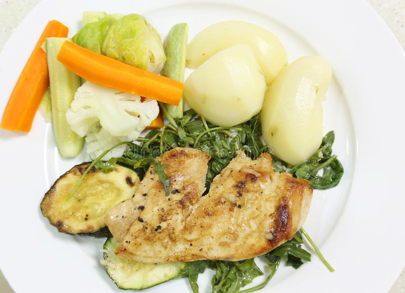 Broiled chicken on rocket and veg. Grilled chicken on a bed of boiled rocket or arugula, served with potatoes and a mixture of steamed vegetables, from above stock photography