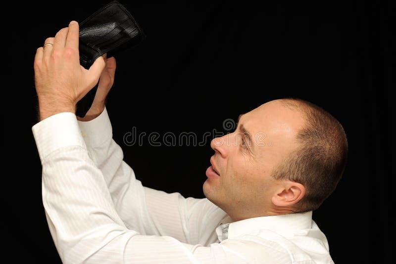 Broke Businessman. A broke businessman checking his empty wallet, on a black studio background stock photos
