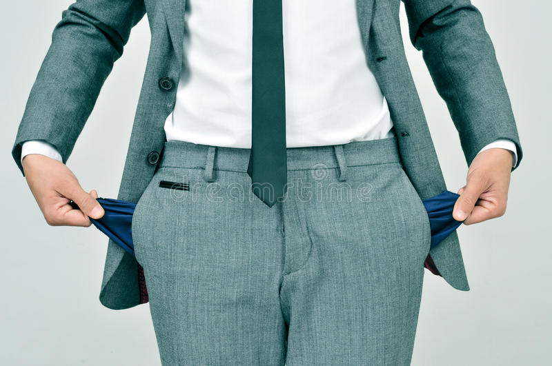 Broke businessman showing his empty pockets stock photography