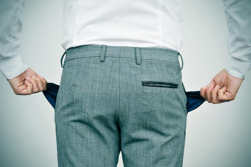 Broke businessman showing his empty pockets stock image