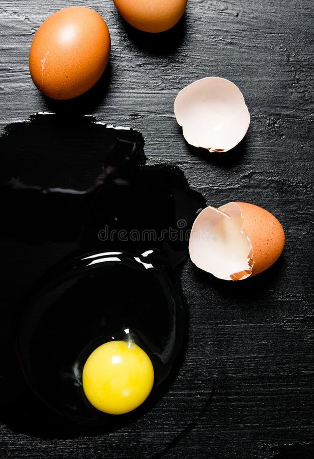 broken ägg på svart träbakgrund royaltyfri bild