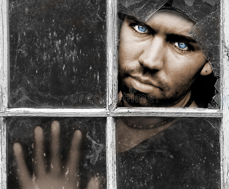 Broken. Young Man with piercing Blue Eyes stares through dirty old broken Window with his Hand pressed against the Glass with room for a message above stock photo