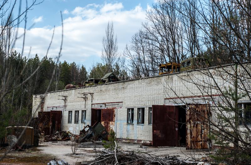 Broken and abandoned machinery in Chernobyl Exclusion Zone. Industrial building with broken cars on the roof stock image