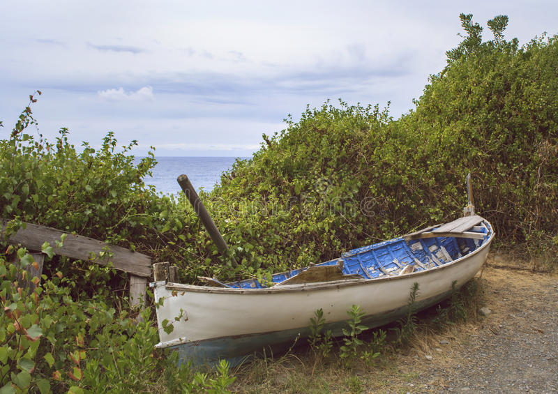 Broken and abandoned row-boat by the ocean. An old, broken and abandoned rowing boat by the ocean stock images