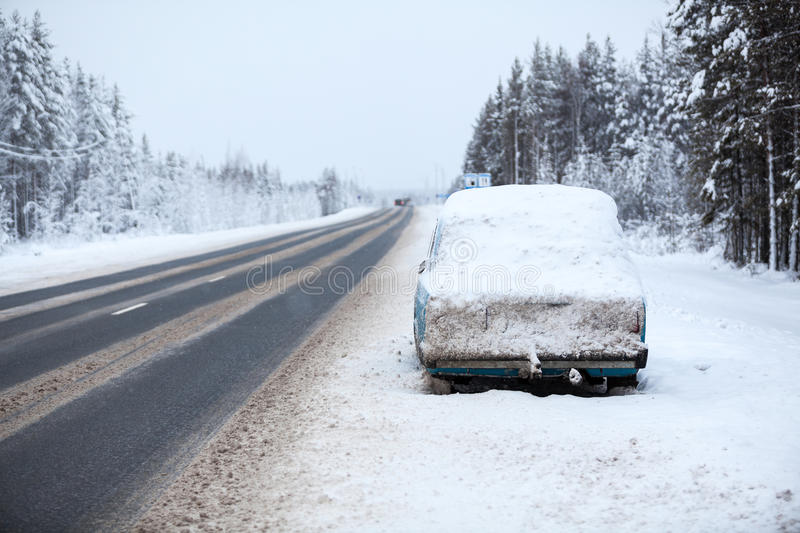 Broken and abandoned vehicle on severe winter road, parking on road curb. The Kola highway to Murmansk city, Karelia, Russia stock image
