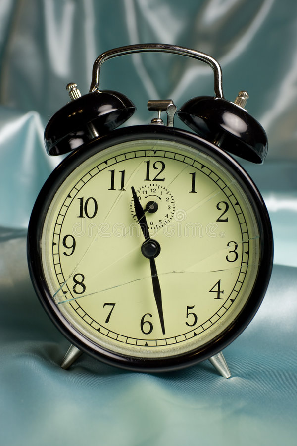 Broken alarm clock. A detail of a black classical alarm clock with broken glass on blue satin royalty free stock photos