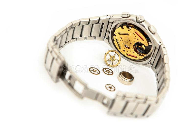 Broken analog wrist watch with visible clockwork. A picture of the broken analog wrist watch with visible clockwork on a white background royalty free stock image