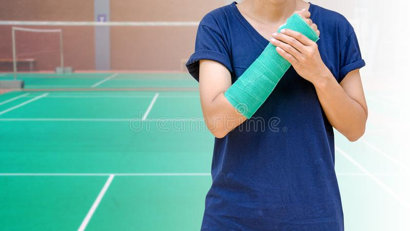 Broken arm bone in green cast isolated on green badminton court.  stock photography
