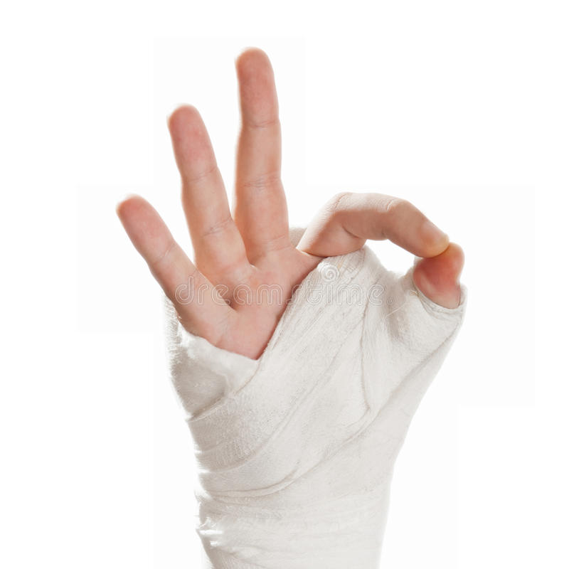 Broken arm in a cast. Fingers show the character all is well - O. Broken arm in a cast on a white background. Fingers show the character all is well - Okay stock photo