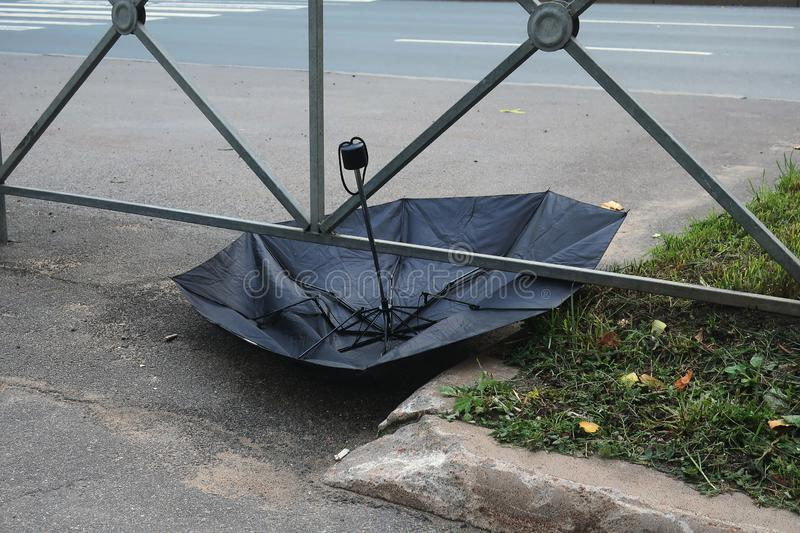 Broken black umbrella thrown by the road royalty free stock photography