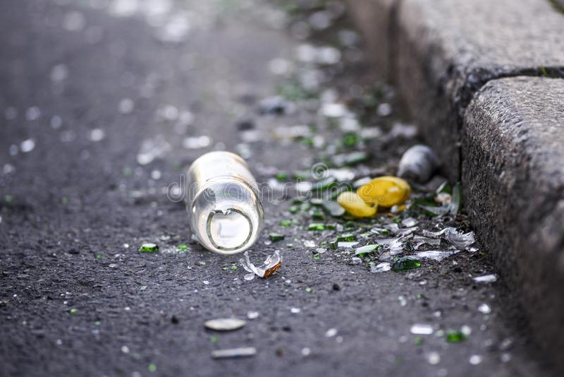 Broken bottle and garbage by the curb on the street stock images