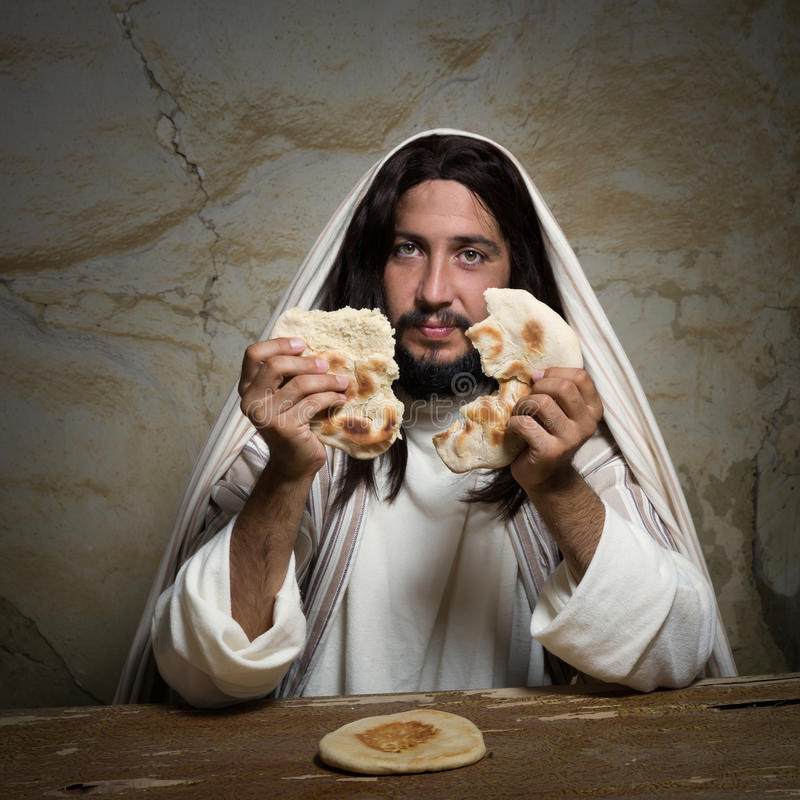 Broken bread at Last Supper. Authentic reenactment scene of Jesus breaking the bread during Last Supper, saying `this is my body royalty free stock image
