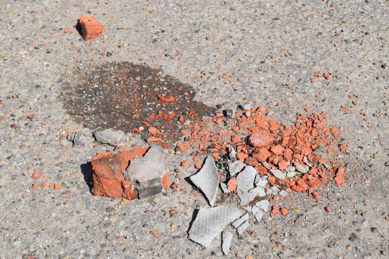 The broken bricks and pieces of slate on asphalt stock photos