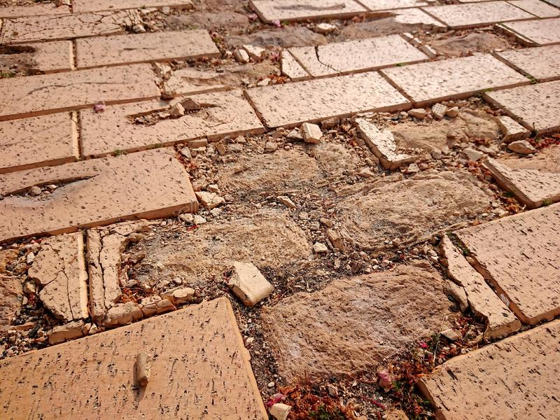 Broken brown tiles of a pavement. Broken brown tiles in a pavement . Broken and chipped off pieces are found nearby stock images