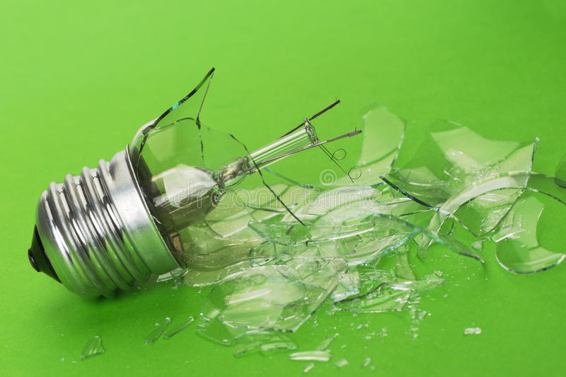 The broken bulb. The brokenbulb. Glass splinters on a green background stock photos