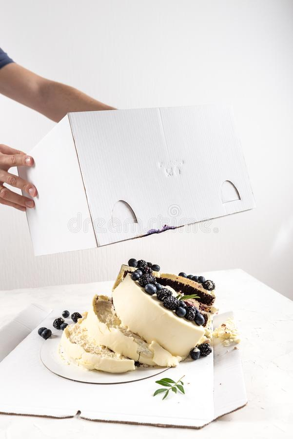 Broken cake inside the box on white background. Bad delivery concept. Spoiled birthday, wedding. Bad luck. Copy space. For text royalty free stock photo