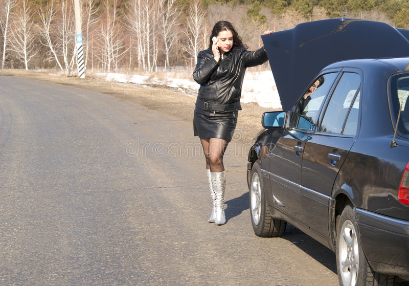 Broken car. Young woman talking on a cell phone, trying to get help with her broken car stock images