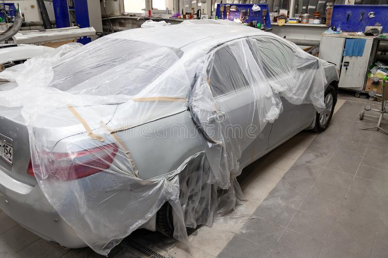 A broken car covered with a protective film from splashing paint in a spray booth in a car body repair shop before it is painted stock images