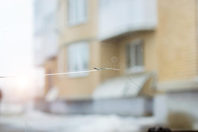 Broken car glass with crack on windshield of auto. Blurred grey backdrop of transport road in background stock photos