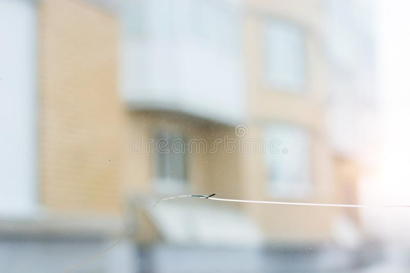 Broken car glass with crack on windshield of auto. Blurred grey backdrop of transport road in background royalty free stock images