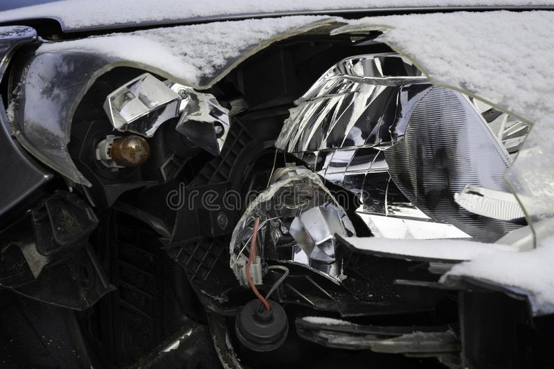 Broken car light accident. Close up of damaged headlight in a front car, winter. stock image