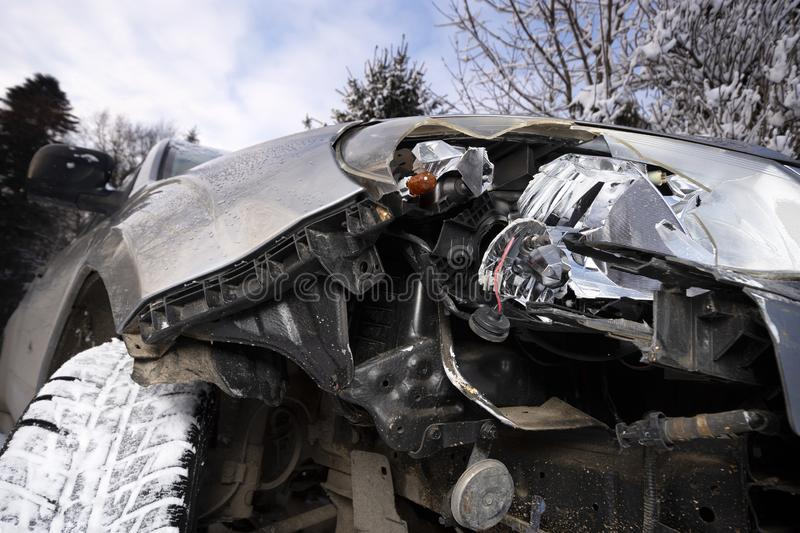 Broken car light accident. Close up of damaged headlight in a front car, winter. stock photography