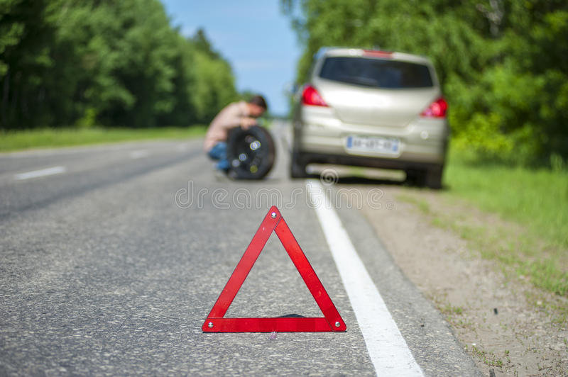 Broken car and male driver changing the wheel. Car after breakdown, red warning sign on the roadside. Male driver changing the tire. Focus on emergency sign stock photo