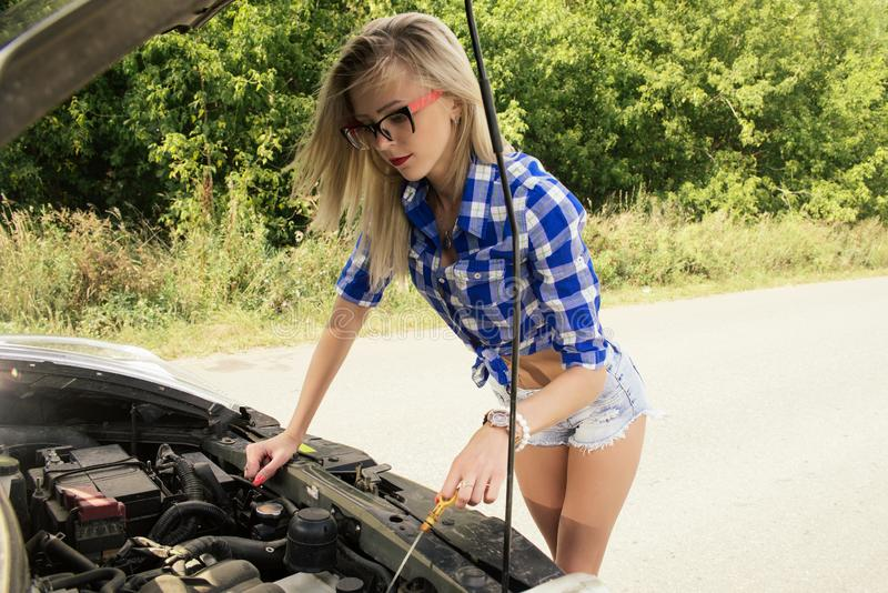 A broken car on the road, the girl checks the oil level stock image
