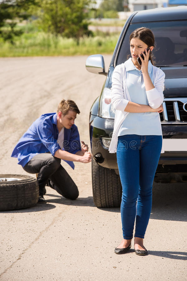 Broken car. Young men changing the punctured tyre on his car stock photo