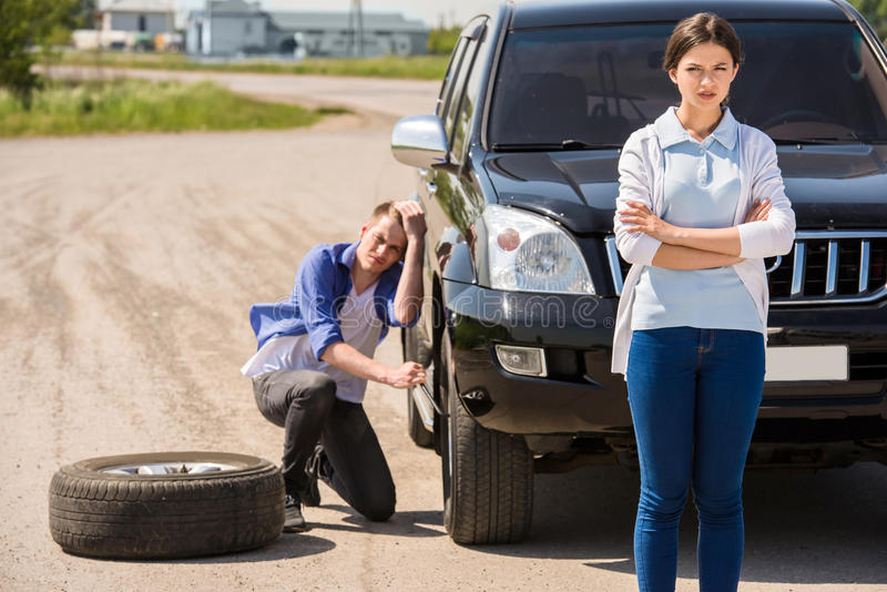 Broken car. Young men changing the punctured tyre on his car stock image