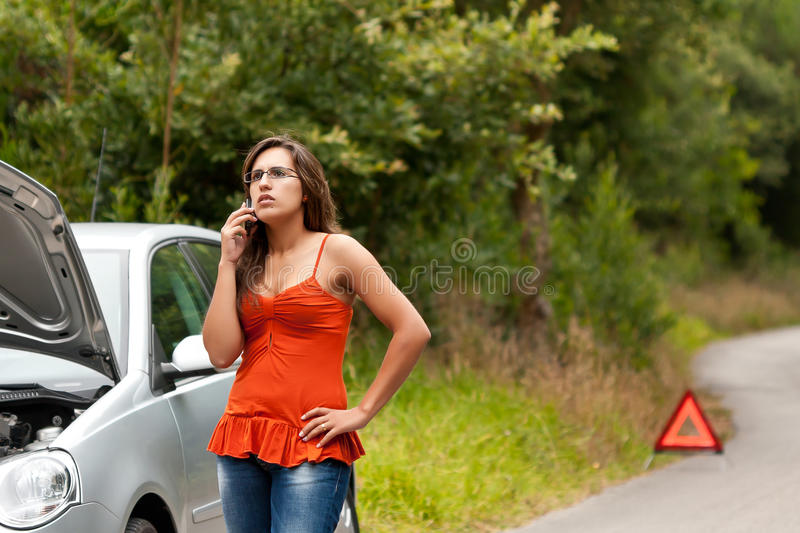 Broken Car - Young Woman Calls for Assistance. A woman calls for assistance using her mobile phone, after her car broke down on the road side stock photo