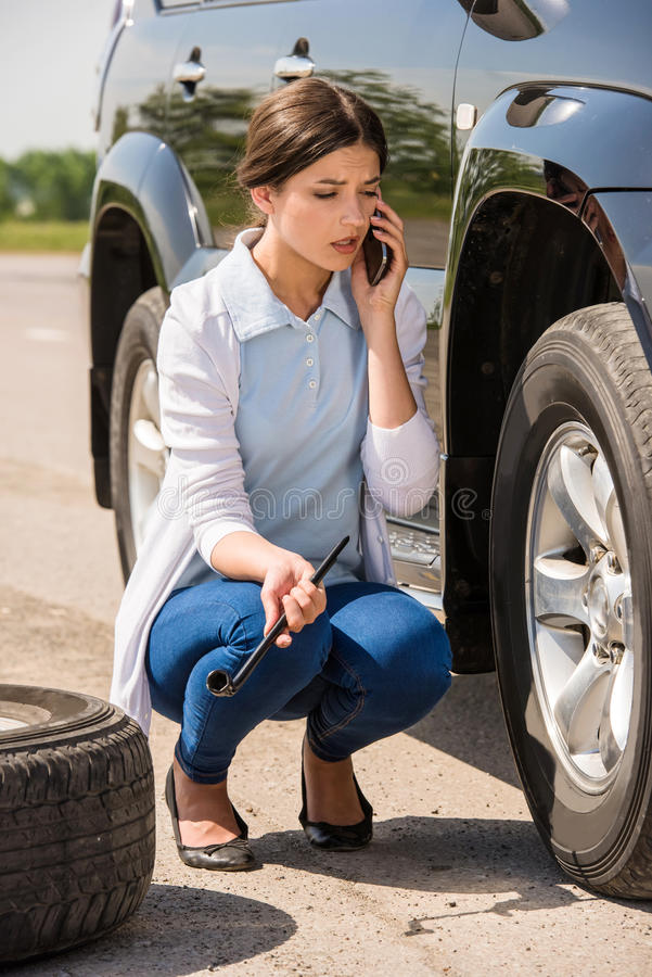 Broken car. Young woman changing the punctured tyre on his car stock photo