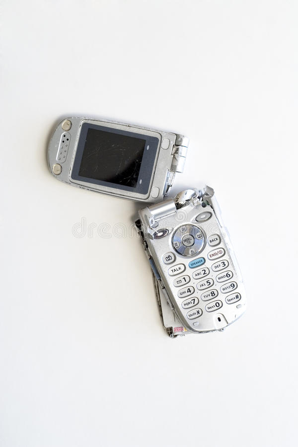 Broken Cell phone. A broken flip-style cell phone, scratched and broken in two royalty free stock photography