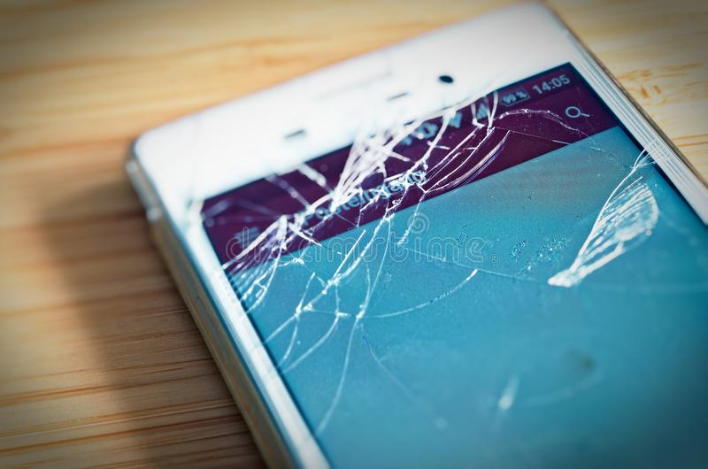 Broken cell phone with display damage and splintered display to symbolize damage to the phone display stock image