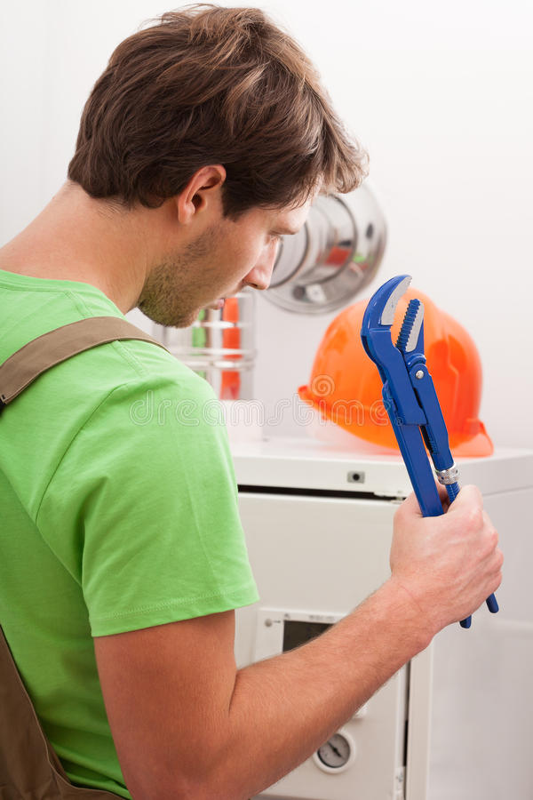 Broken central heating boiler. And man with wrench royalty free stock images