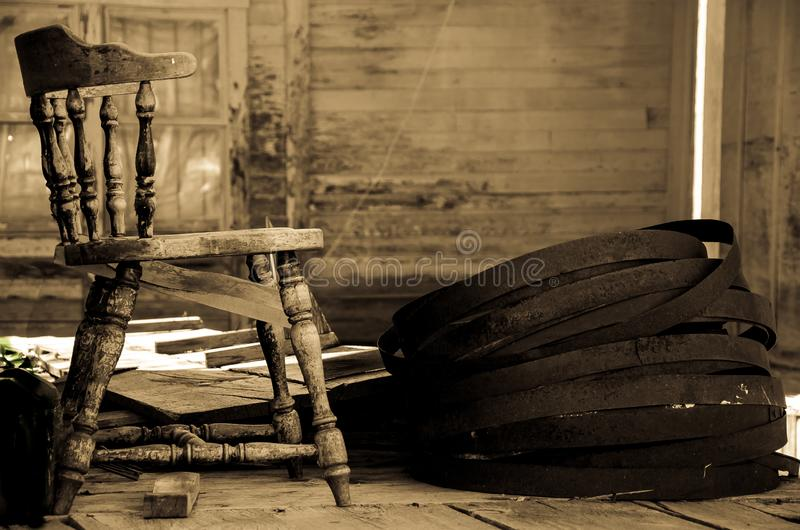 Broken Chair on the Cabin Porch. Sepia view of a broken chair and barrel hoops on the porch on an abandoned cabin royalty free stock photos