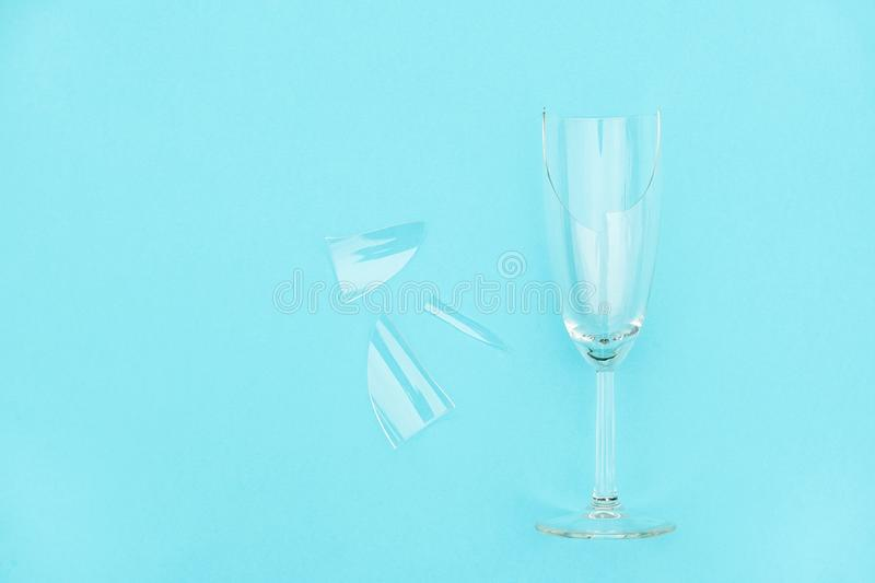 Broken champagne glass with splinters on blue background with copy space. Concept fight against alcoholism, drunkenness and royalty free stock photography