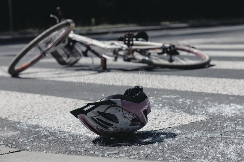 Broken child`s helmet and bike on pedestrian crossing after accident royalty free stock photography