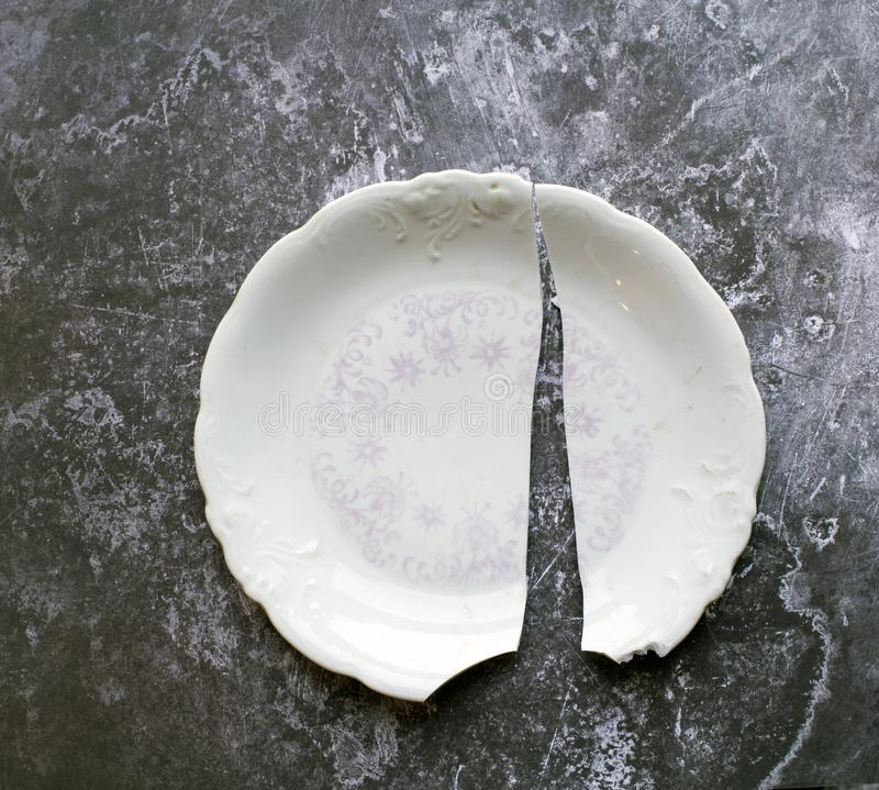 Fractured. Broken and chipped antique white plate against a gey grunge background stock photo