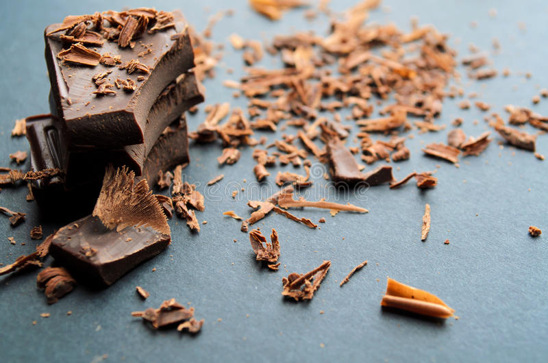 Broken chocolate bar. Chips and powder. Shallow depth of field stock image