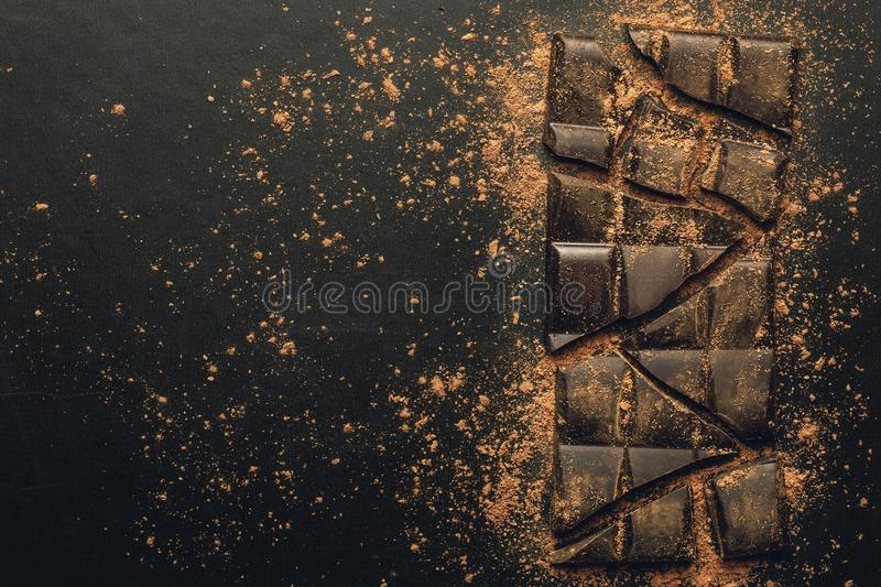 Broken chocolate bar to pieces and cocoa powder on dark background, top view with copy space royalty free stock photos