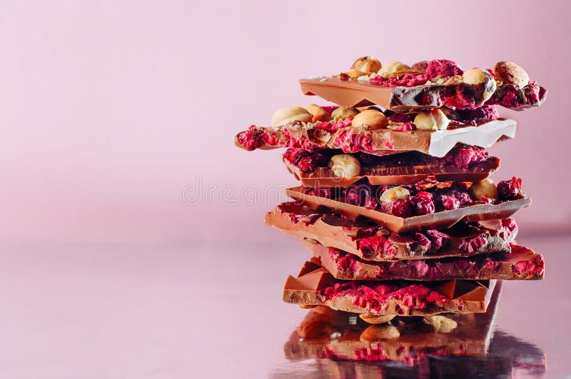Broken chocolate bars decorated with nuts and raspberry on pink royalty free stock images